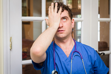 Male nurse in scrubs with stethoscope makes huge mistake