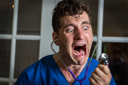 lunatic: Crazy lunatic male nurse yells into his own stethoscope Stock Photo