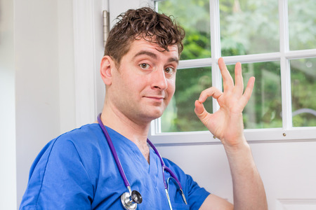 Male nurse in scrubs with stethoscope making okay hand sign Stock fotó