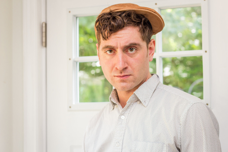 newsboy cap: Young handsome curly haired man wearing newsboy hat
