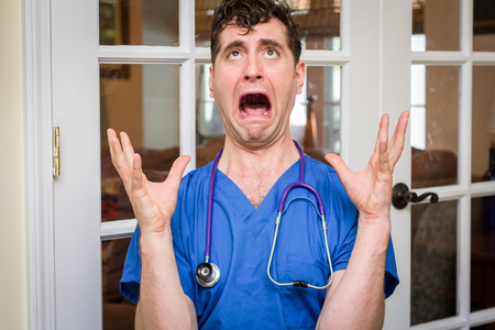 Male nurse in scrubs with stethoscope overwhelmed and panic stricken Stock Photo