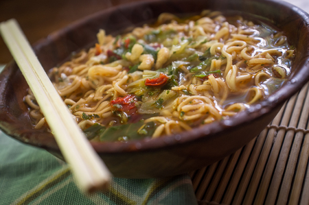 chopsticks: Spicy asian ramen noodle soup with chopsticks in wooden bowl