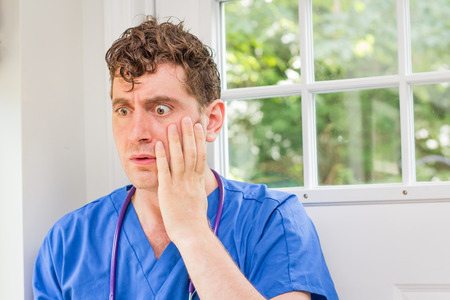 adult oops: Male nurse in scrubs with stethoscope makes huge mistake