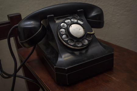 hangup: Old vintage rotary dial telephone on wooden desk Stock Photo