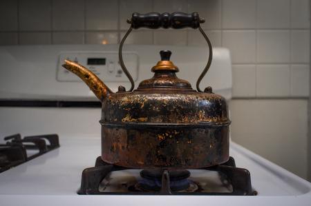 stovetop: Antique old rusty tea pot on kitchen stove Stock Photo