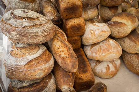 bakery products: Many different types of fresh bakery bread in background