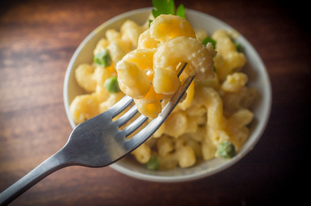Delicious macaroni and cheddar cheese with parsley sprig Imagens