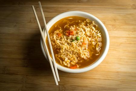 chopsticks: Spicy asian ramen noodle soup with chopsticks Stock Photo