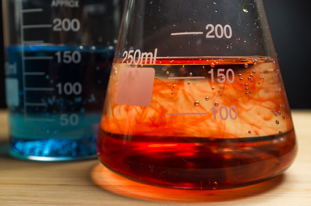 reagents: Close up glass measuring beaker for science experiment background Stock Photo