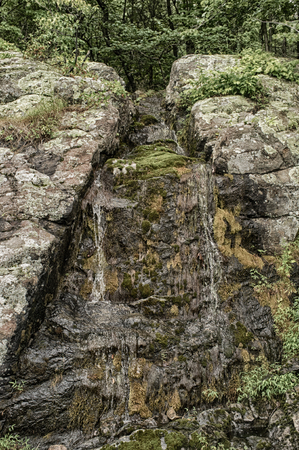 trickle: Beautiful springtime waterfall trickle on ancient rock wall