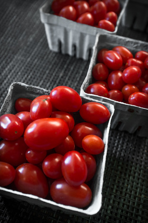 Baskets of fresh organic red grape tomatoes at local farmers market