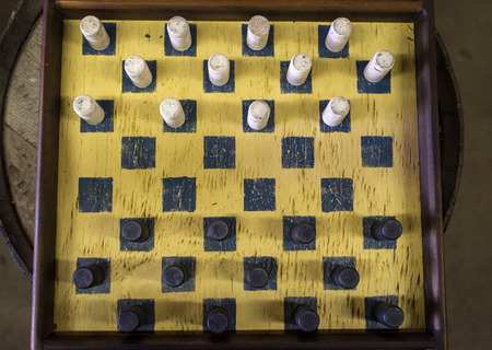 checkers: Rugged old dirty antique checkers board and pieces