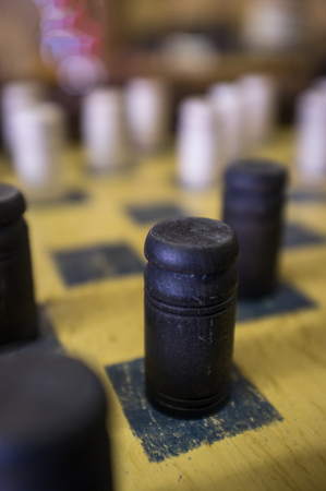 Rugged old dirty antique checkers board and pieces