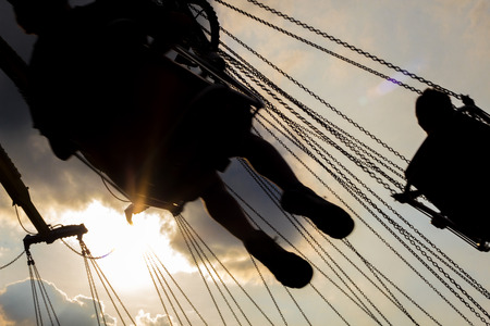 fairground: Fairground swing ride at dusk with sunset silhouette
