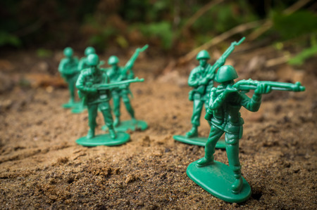 plastic soldier: Green toy soldiers march forward ready for battle Stock Photo