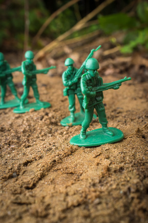Green toy soldiers march forward ready for battle Stock Photo