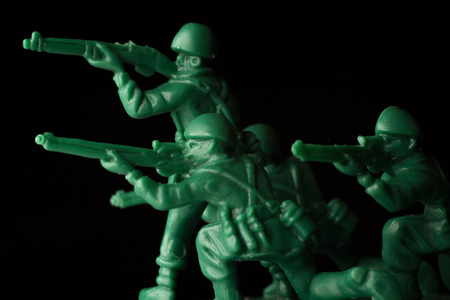 green plastic soldiers: Dramatic green toy army soldiers lined up for battle Stock Photo