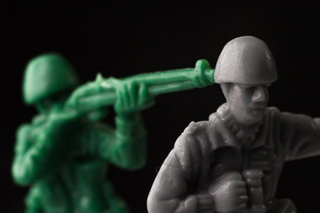 enemy: Green toy soldier surprises enemy from behind Stock Photo