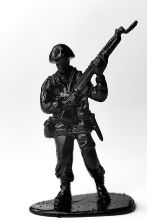 plastic soldier: Dramatic toy army soldier carrying rifle to battle in black and white image Stock Photo