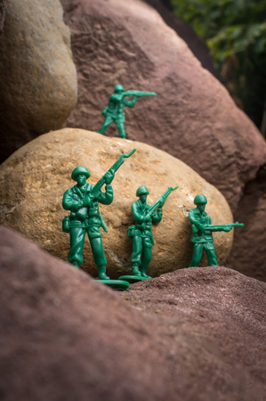 green military miniature: Toy soldiers march along rocky cliffs in natural environment
