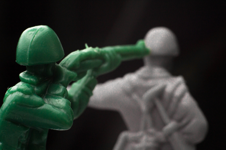 Green toy soldier surprises enemy from behind Stock Photo