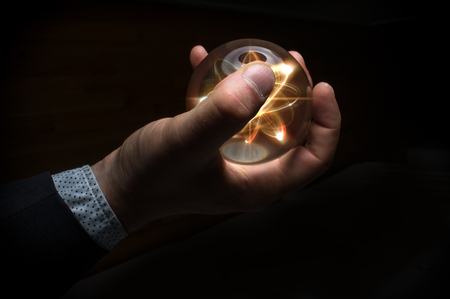 nucular: Holding atom in fortune teller magic crystal ball Stock Photo