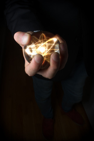 psychic: Holding atom in fortune teller magic crystal ball Stock Photo