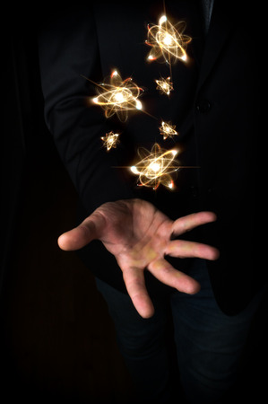 nucular: Several atoms float above mans open hand