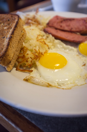 Eggs sunny side up toast and sausage American breakfast