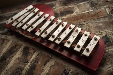 xylophone: Old xylophone hangs on grunge brick wall outside club