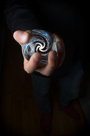 seer: Hands holding magic crystal ball with smoky hypnosis spiral