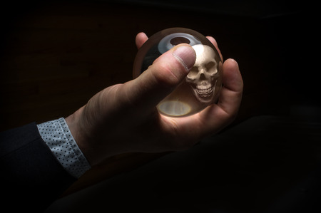 Holding magic crystal ball with skull predicting death