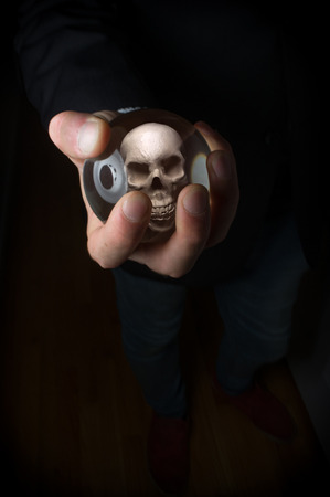 tell fortune: Holding magic crystal ball with skull predicting death