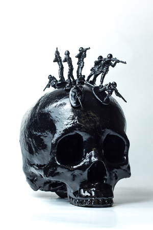 plastic soldier: Black skull with toy soldiers forming war mohawk on top
