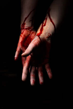 Bloody hands emerge from the darkness in horror Halloween image Stock Photo