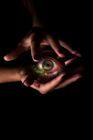 third eye: Female hands hold crystal ball with third eye for fortune telling background
