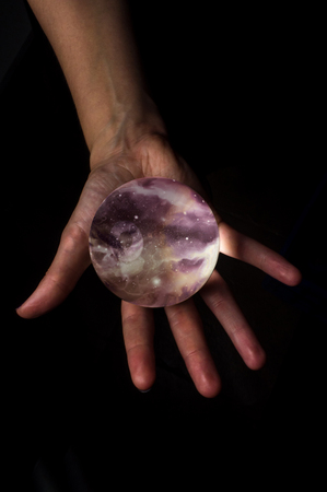 starscape: Female hands hold crystal ball with starscape for fortune telling background