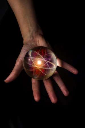 nucular: Female hands hold crystal ball with atom particle for fortune telling background Stock Photo
