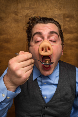 slob: Silly pig man eating lose change for banking greed image Stock Photo