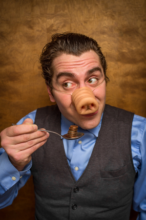 Silly pig man eating lose change for banking greed image Stock Photo