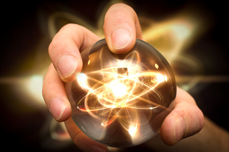 Holding atom in fortune teller magic crystal ball Stock Photo