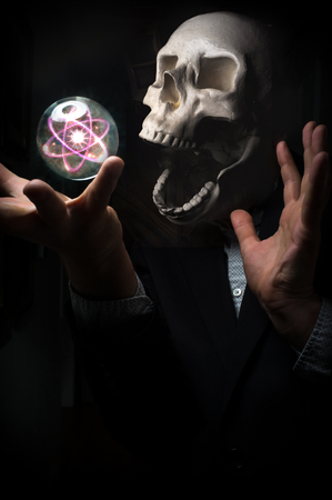 nucular: Angel of death holding magic crystal ball atom Stock Photo