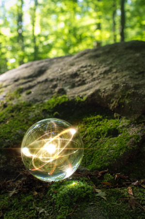 nucular: Magic crystal ball atom on forest floor for summer fantasy imagery Stock Photo