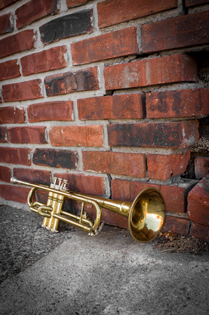 Old worn trumpet stands alone against a grungy brick wall Banco de Imagens