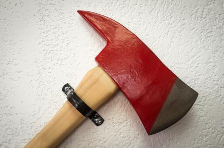 ax man: Closeup of firemans red axe hanging on textured wall