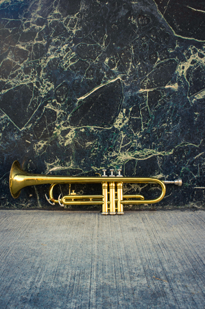 marble wall: Old worn trumpet stands alone against a grungy marble wall