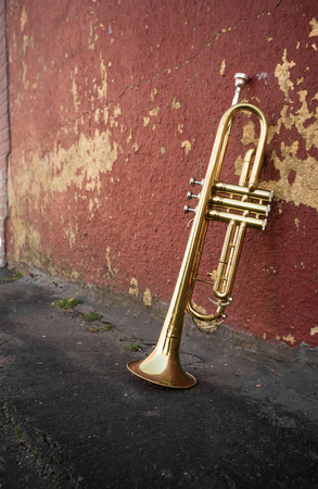 pealing: Old worn trumpet stands alone against a grungy pealing brick wall Stock Photo
