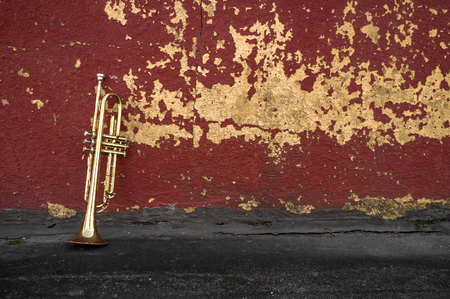 pealing: Old worn trumpet stands alone against a grungy pealing red wall