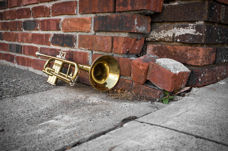 pealing: Old worn trumpet stands alone against a grungy brick wall Stock Photo