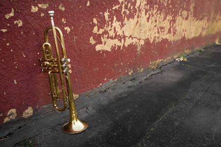 Old worn trumpet stands alone against a grungy pealing brick wall Banco de Imagens